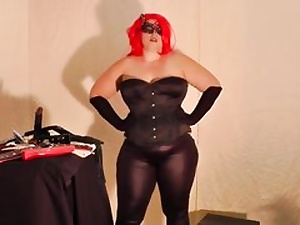 Horny goddess dressed in leather and a crimson wig about to pleasure her cunny
