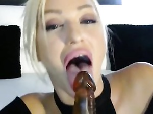 Posh blonde is toying with a thick fake penis slurping it all over